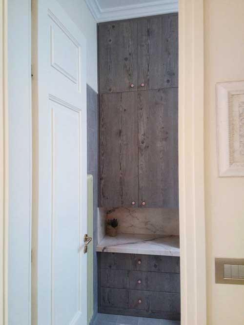 συρταριέρα μπάνιου με πάγκο μαρμάρινο και απο πάνω δίφυλλή ντουλάπα με κρθφά στηρίγματα